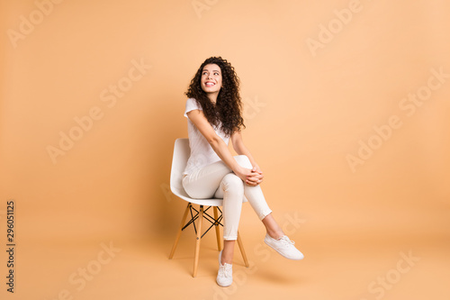 Fototapeta Full length photo of amazing lady looking interested empty space sitting comfy chair good mood inspired wear casual clothes isolated beige pastel color background obraz