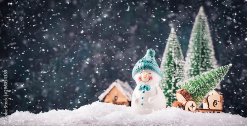 Merry Christmas and happy New Year composition with copy space. Little snowman carries Christmas tree from fairy forest to home. Winter festive background