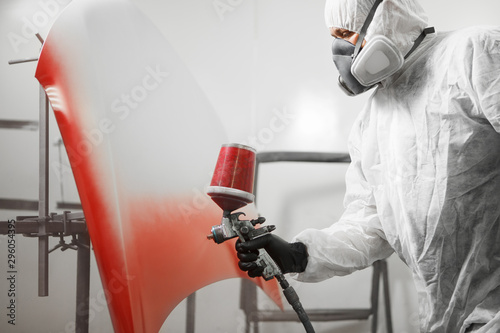 Fototapeta Male worker in protective clothes and mask painting hood of car using red spray paint. obraz