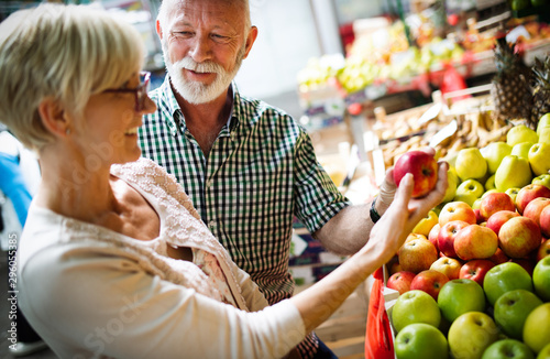 Portrait of beautiful elderly couple in market buing food Fototapeta
