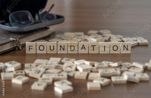 Fotografering The concept of Foundation represented by wooden letter tiles