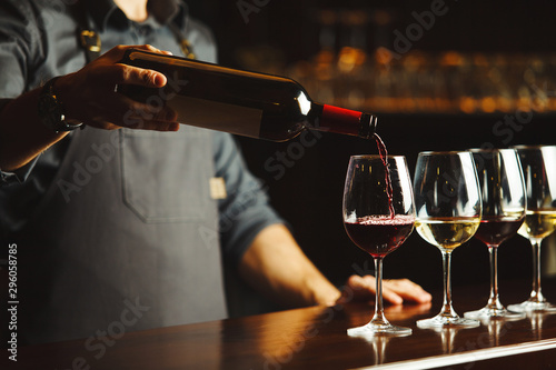 Carta da parati  Bartender pours red wine in glasses on wooden bar counter