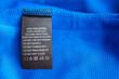 Leinwandbild Motiv Black laundry care washing instructions clothes label on blue jersey polyester sport shirt