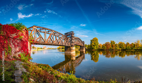 Cadres-photo bureau Europe de l Est Cityscape of old railway metal rusty bridge in red ivy leaves over Elbe river in downtown of Magdeburg in Autumn colors, Germany