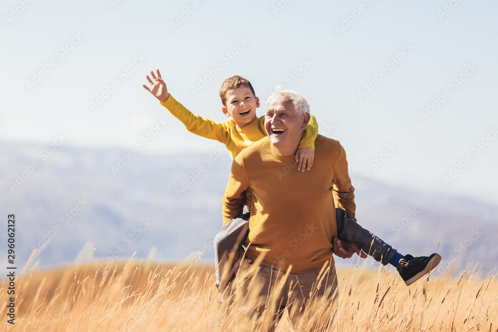 Fototapety, obrazy: Grandson piggyback with his grandfather in autumn.