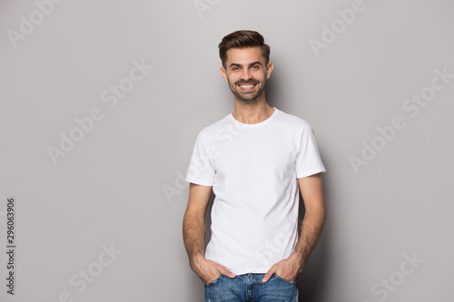 Fototapeta  Smiling Caucasian man posing on grey studio background