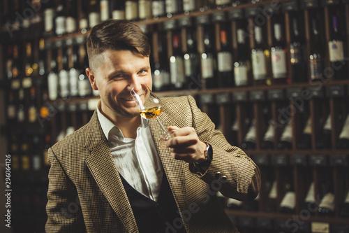 Fotomural Smiling sommelier in the wine cellar tasting whiskey.