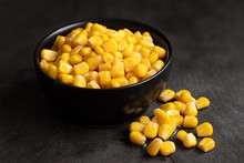 Canned Sweet Corn In A Black Ceramic Bowl Isolated On Black Slate Next To Spilled Sweet Corn.