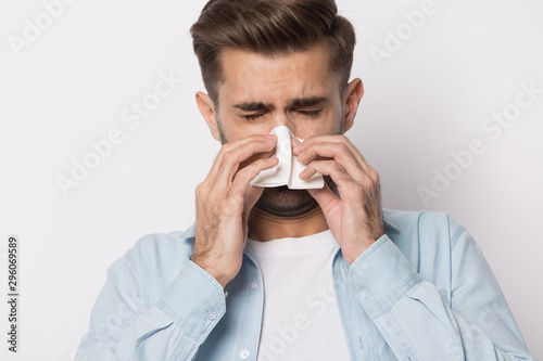 Obraz na plátne  Unhealthy caucasian man blow nose suffer from flu