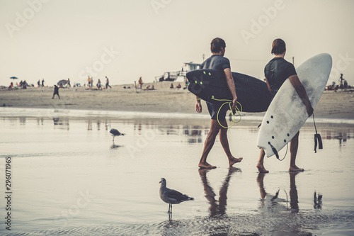 Foto  Surfers are returning from the ocean after active surfing in the waves