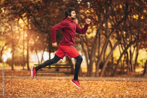 Young man running at park during autumn morning Fototapet