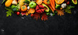 Leinwandbild Motiv Autumn vegetables and fruits on a black stone background: Pumpkin, tomatoes, corn, pomegranate, persimmon, apple. Top view. Free copy space.