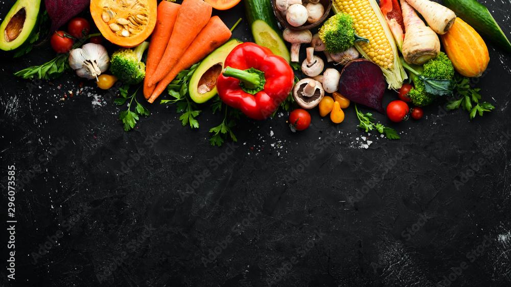 Fototapeta Fresh seasonal vegetables on a black stone background: Pumpkin, tomato, avocado, cucumber, onion, carrot. Autumn food. Top view. Free copy space.