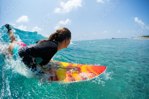 fototapeta na szkło Young woman surfer takes off and starts riding the ocean tropical wave. The surf spot named Chickens in Maldives