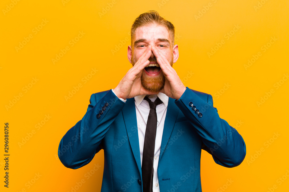 Fototapeta young red head businessman feeling happy, excited and positive, giving a big shout out with hands next to mouth, calling out against orange background