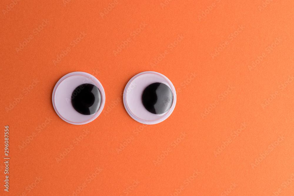 Fototapety, obrazy: Googly eyes on orange background. Minimal holiday concept.