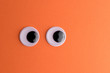 Leinwanddruck Bild - Googly eyes on orange background. Minimal holiday concept.