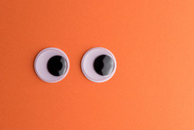 Googly Eyes On Orange Background. Minimal Holiday Concept.