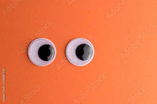 Googly eyes on orange background. Minimal holiday concept. Fototapeta