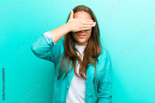 young woman covering eyes with one hand feeling scared or anxious, wondering or Canvas Print