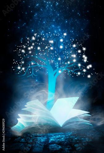 Fototapeta Dark night magic scene. An open book, a garland of old keys, a magic tree of knowledge. Night view, smoke, magic, magical experience, a fabulous night. Blue neon, moonlight at night. Wet asphalt, refl obraz na płótnie