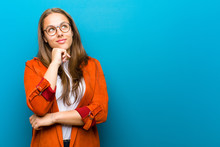 Young Woman Feeling Thoughtful, Wondering Or Imagining Ideas, Daydreaming And Looking Up To Copy Space Against Blue Background