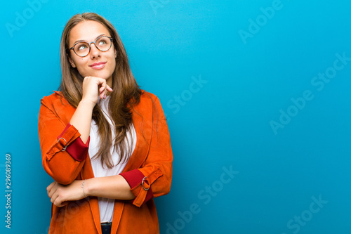 Fotomural  young woman feeling thoughtful, wondering or imagining ideas, daydreaming and lo