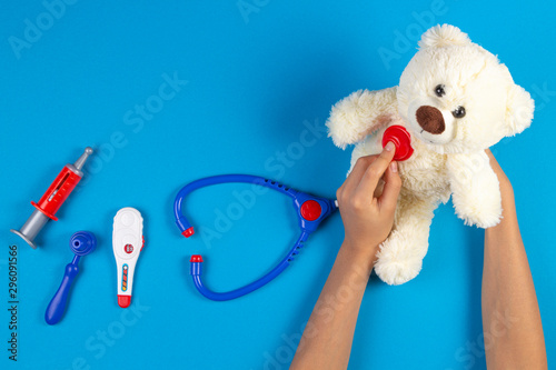 Kid hands with toy stethoscope, teddy bear and toy medicine tools on light blue background. Children doctor, medicine concept