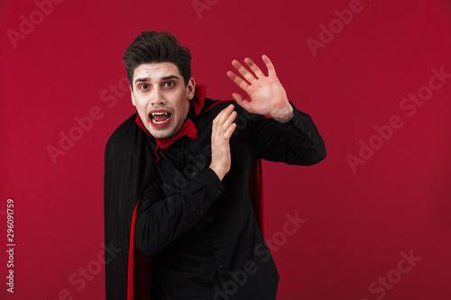 Fotografia, Obraz Image of displeased vampire man in black halloween costume being scared