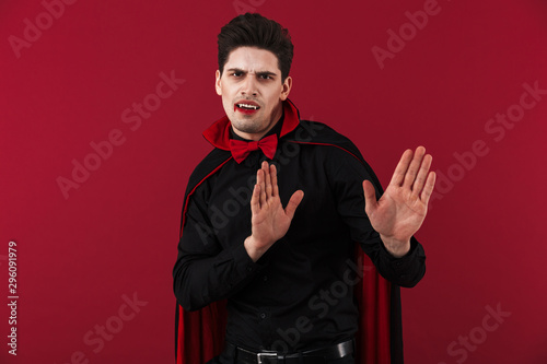 Photo Image of dissatisfied vampire man with fangs in black halloween costume