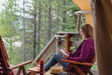Glamping Trip - Woman Sitting And Relaxing Outside Luxury Tent In Montana