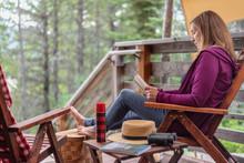 Woman Sitting Outside Cabin In...
