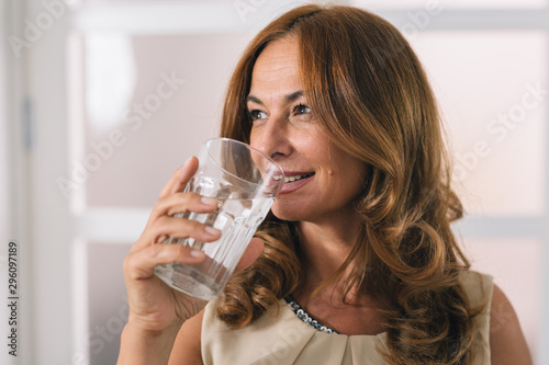 portrait of mid aged woman holding glass of water Fototapet