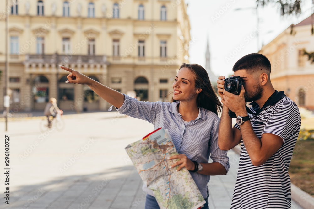 Fototapeta couple tourist in sightseeing in city using paper map and taking pictures with camera