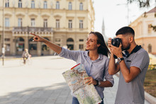 Couple Tourist In Sightseeing In City Using Paper Map And Taking Pictures With Camera