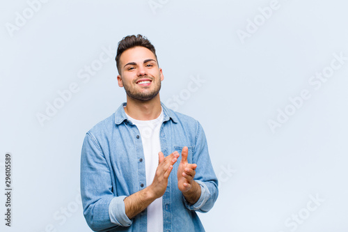 Pinturas sobre lienzo  young hispanic man feeling happy and successful, smiling and clapping hands, say