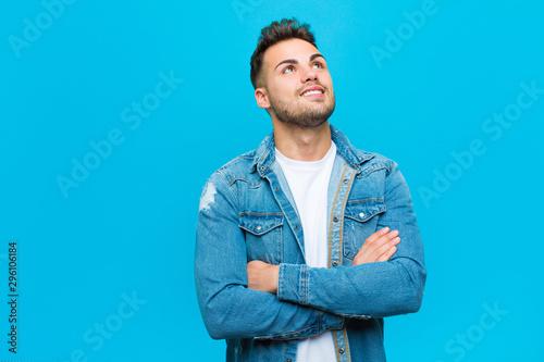 Fotografie, Obraz  young hispanic man feeling happy, proud and hopeful, wondering or thinking, look