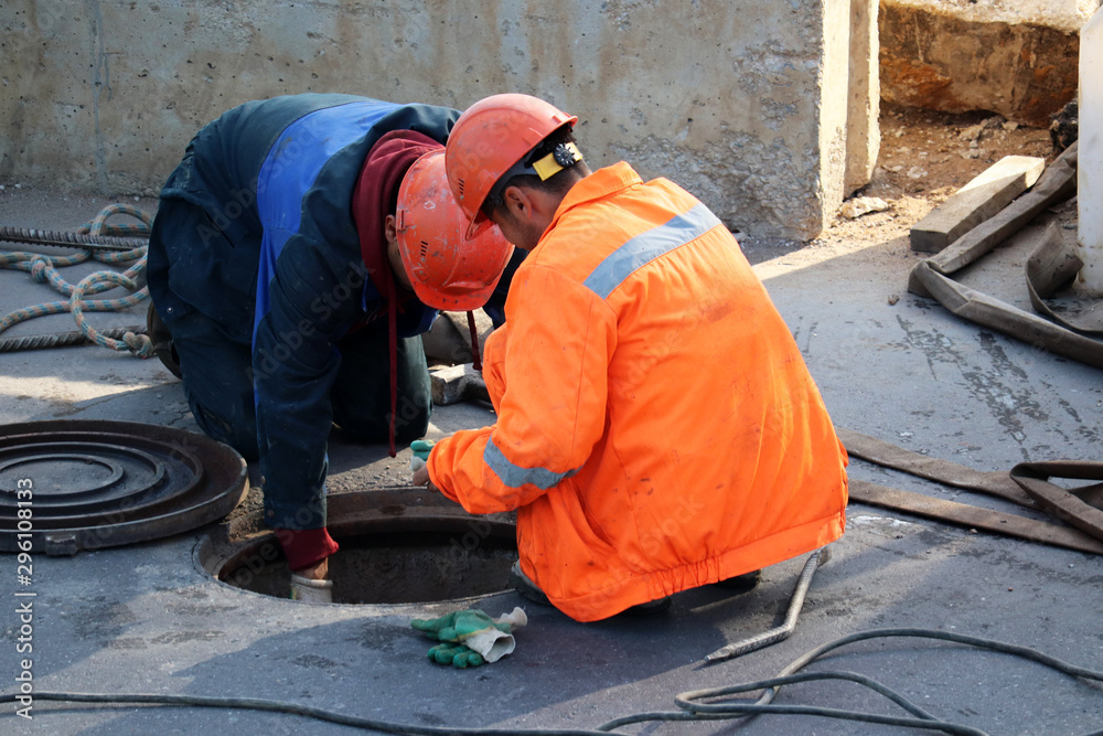 Fototapety, obrazy: Workers over the open sewer hatch on a street. Concept of repair of sewage, underground utilities, water supply system, cable laying, water pipe accident