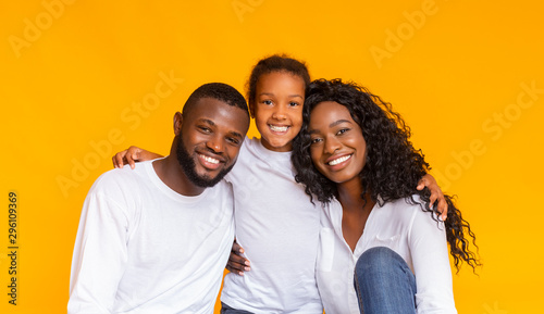 Smiling African American father, mother and daughter over yellow background - 296109369