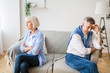 Senior couple after argument sitting on opposite sides of sofa