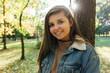 Uśmiechnięta dziewczyna stoi w parku.