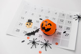 halloween, decorations and holidays concept - jack o lantern, spiders, bats and calendar on white background