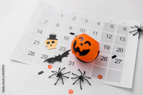 halloween, decorations and holidays concept - jack o lantern, spiders, bats and calendar on white background - 296111175