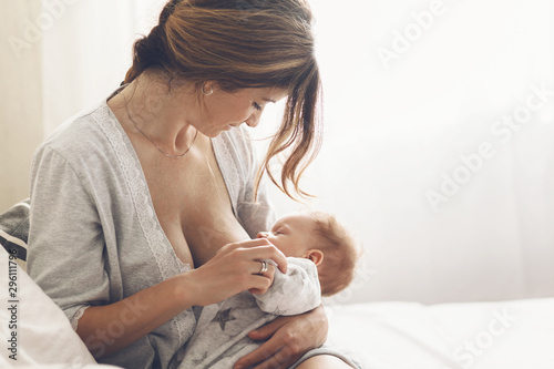 Obraz Loving mom breastfeeding her newborn baby at home - fototapety do salonu