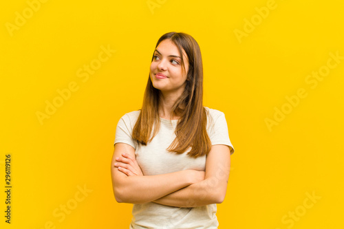 Fotografie, Obraz  young pretty woman feeling happy, proud and hopeful, wondering or thinking, look