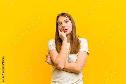 Fototapeta young pretty woman open-mouthed in shock and disbelief, with hand on cheek and arm crossed, feeling stupefied and amazed against orange background obraz na płótnie