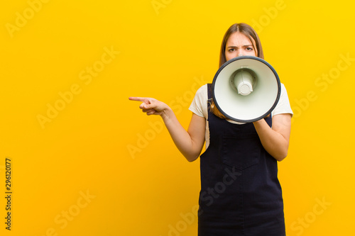 young pretty woman  with a megaphone against orange background Canvas Print