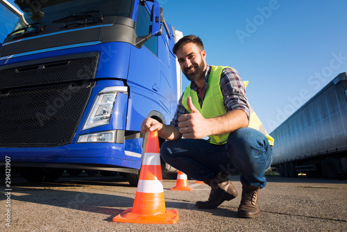 Shot of bearded man learning how to drive truck at driving schools. Truck driver candidate training for driving license. Standing by the traffic cone in reflective vest. Truck in the background.