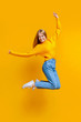 Joyful teen girl jumping in air on orange background