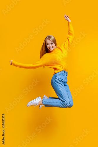 Pinturas sobre lienzo  Joyful teen girl jumping in air on orange background